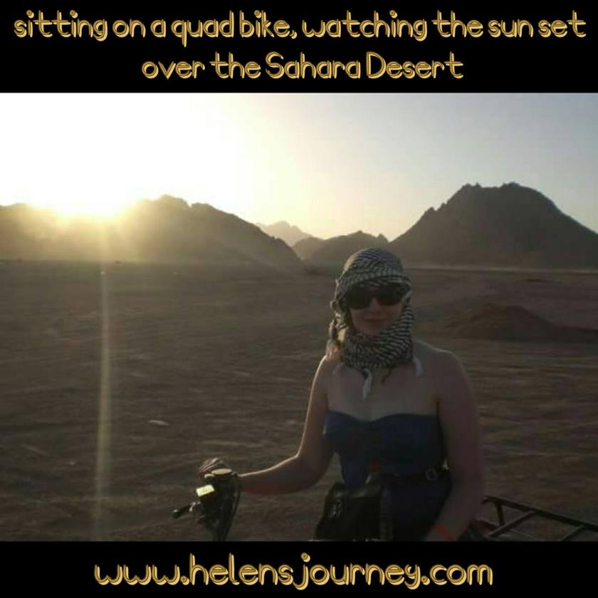 Helen's Journey Blog sitting on a quad bike watching the sun set over the sahara desert