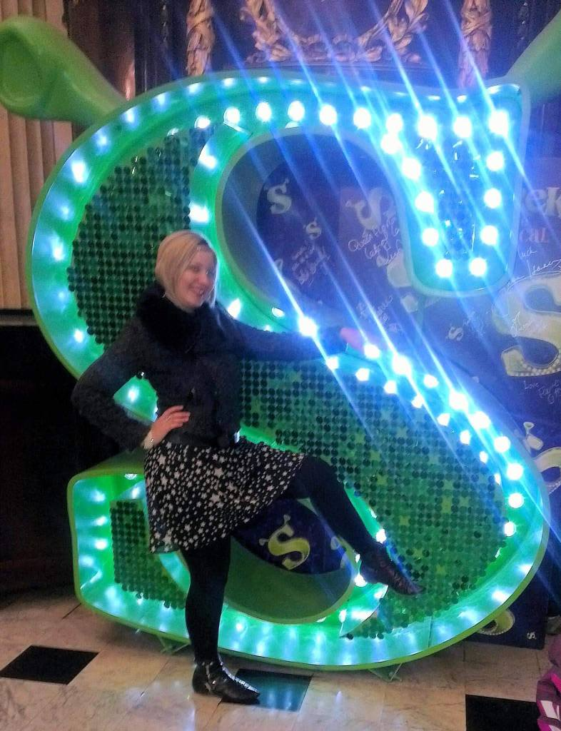 blogger Helen's Journey posing with a giant S for Shrek the musical